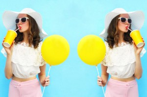Fashion pretty woman in straw hat with air balloon drinks fruit juice from cup over colorful blue background